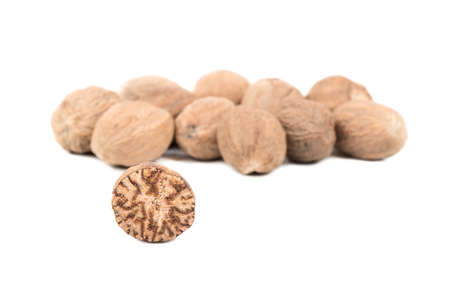 Half of a nutmeg with a bunch of nuts on a white background