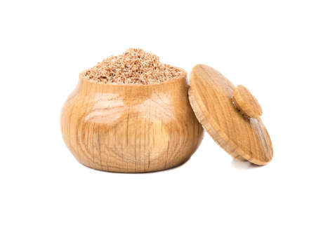 Nutmeg in a wooden jar for spice isolated on white Stock Photo