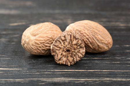 Dry nutmeg with half on wooden background
