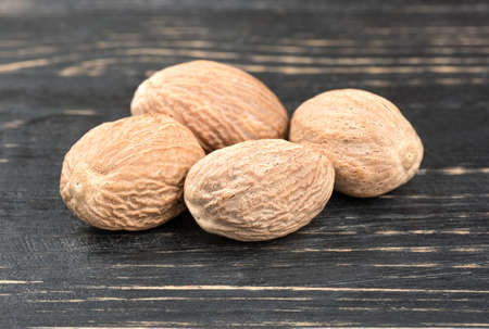 Certains noix de muscade sèches sur fond de bois foncé Banque d'images - 80571728