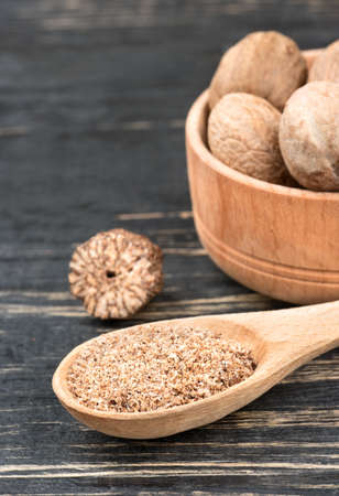 Nutmeg powder in a spoon with a bowl of nuts on wooden background closeup Stock Photo