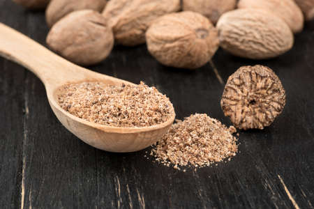 Nutmeg powder in a spoon with scattered nuts on wooden background