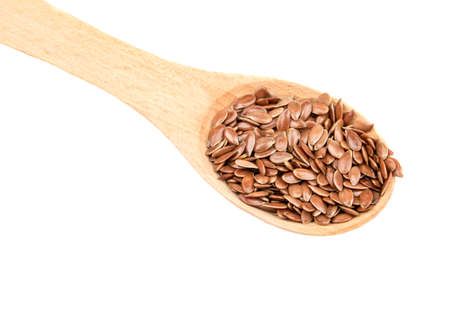 Flax seeds in wooden spoon isolated on white background closeup