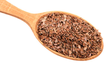 dietary fiber: Flax seeds in wooden spoon on white background, closeup Stock Photo