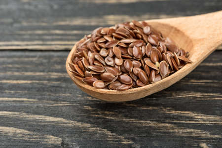 Raw flax seeds in a small spoon on wooden background closeup