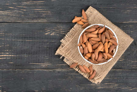 Uzbek almonds in the bowl on a burlap and wood background, top view