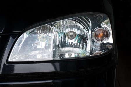 shiny car: Headlight of a black car close up
