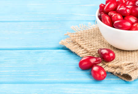 Fresh dogwood berries in the bowl on the table and sacking, closeup Stock Photo