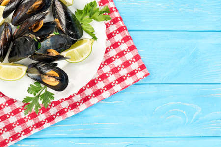 Plate with mussels, lime and parsley on a towel and a blank table Stock Photo