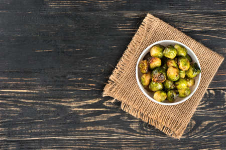 Bowl with fried Brussels sprouts on sackcloth and empty wooden background