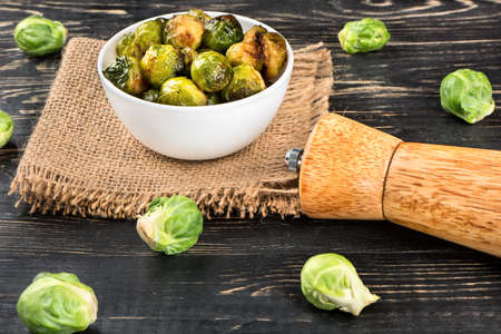 Bowl with fried Brussels sprouts and ingredients on a wooden background