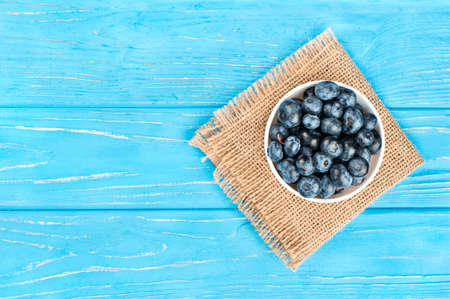 Bowl filled with blueberries on sackcloth and empty wooden background, top view Stock Photo