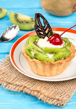 Delicious fruit cake with kiwi on sackcloth and table