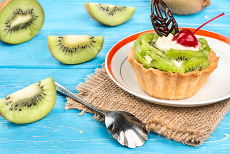 Delicious fruit cake with kiwi on a plate, and sackcloth and table Stock Photo