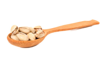 Pistachio nuts in spoon isolated on white background