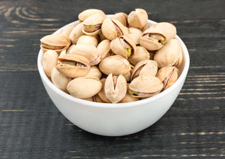 Ceramic bowl filled with salty pistachio nuts on a table