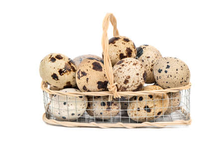 Raw quail eggs in an iron basket on a white background Stock Photo
