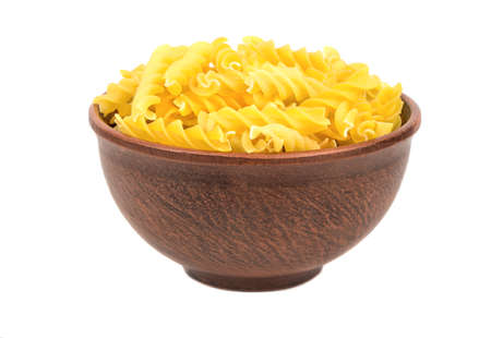 Uncooked pasta fusilli in a bowl on white background