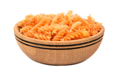Uncooked pasta fusilli in a wooden bowl on a white background Stock Photo