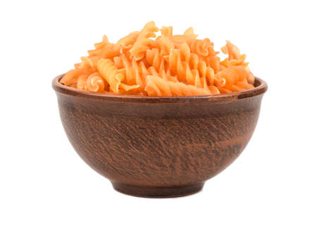 Uncooked pasta fusilli in a bowl isolated on white background