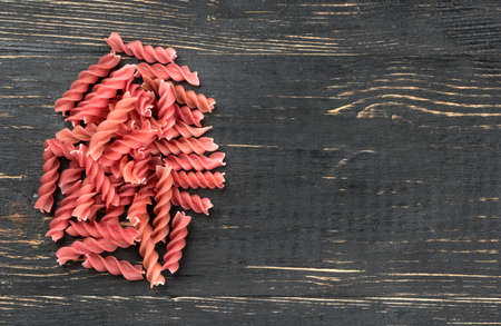 Small bunch of red pasta fusilli on an empty wooden background
