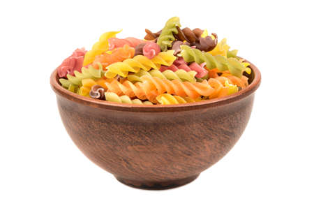 Raw colored pasta fusilli in a bowl on white background