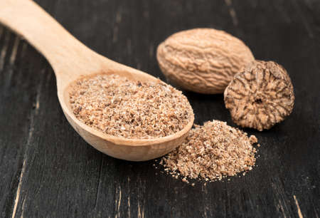 Nutmeg powder in a spoon with a half of a walnut on wooden background Stock Photo