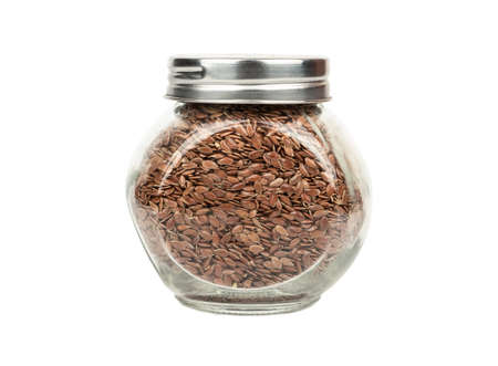 Glass jar filled with flax seeds on white background Stock Photo