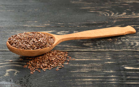 Spoon with flax seed and scattered grain on the table