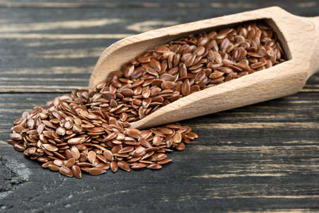 linseed: Flax seeds in the scoop on wooden background closeup