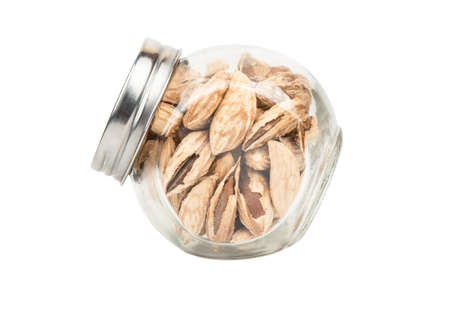 Wild uzbek almonds in a jar isolated on white background