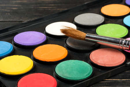 Palette with paints and brush, closeup on the table