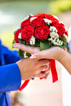 Bride and groom holding wedding bouquet closeup