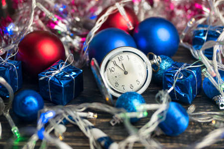 Christmas balls scattered on a wooden background with old clock of the approaching new year