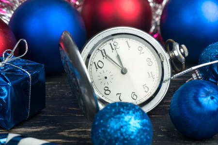 Old clock showing the approach of the new year with Christmas balls closeup