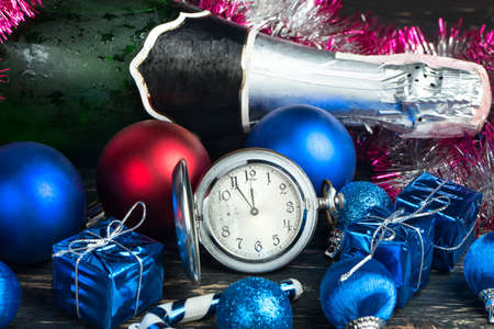 Christmas balls, decorations, bottle of champagne and watch on wooden background