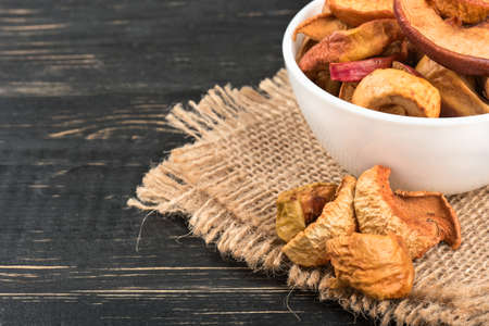 Bowl of dry Apple slices on sackcloth and wooden background