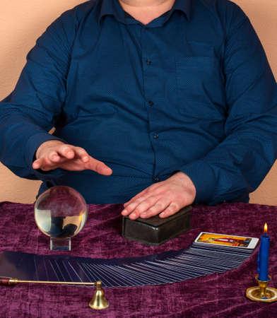 Homem cheio adivinhando em cartões de Taro e a bola mágica Foto de archivo