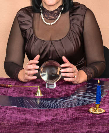 Female fortune teller looks in the future magic ball