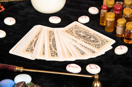 Tarot cards with runes and magical attributes on the table