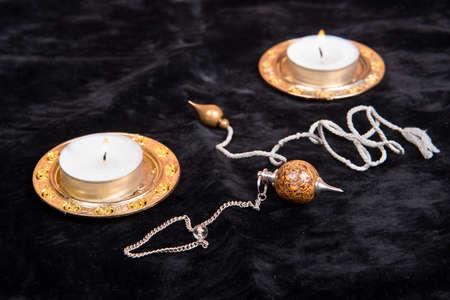 촛불이 어두운 배경에있는 마법 진자