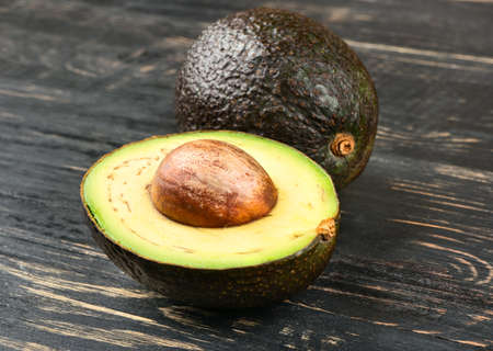 Fresh Hass avocado with a half of a closeup on the table Stock Photo