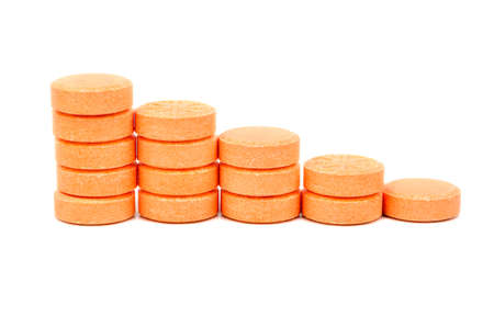Steps from the orange pills on white background Imagens