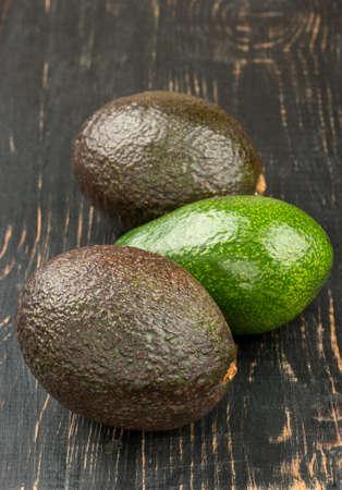 Three fruit avocado close up on a dark table