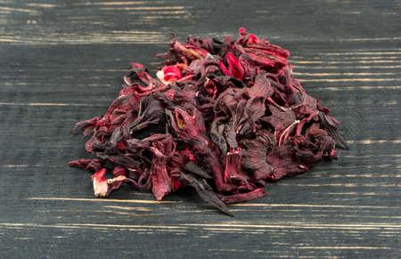 Heap of dry tea hibiscus on a dark table closeup