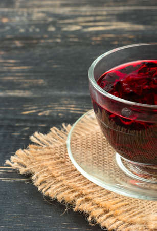 Cup of hot tea hibiscus on a burlap and wood background Stock Photo