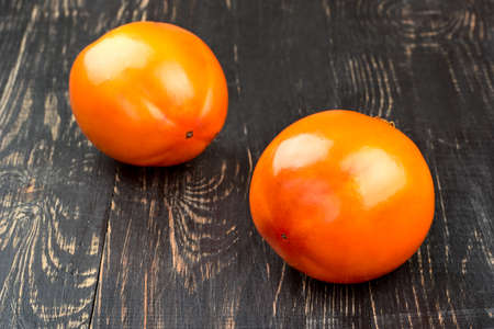 Two fresh persimmon fruit on wooden background