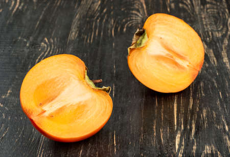 Two halves of juicy fruit persimmons on dark table