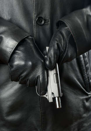 Bandit in black clothes and gloves reloads the gun Stock Photo