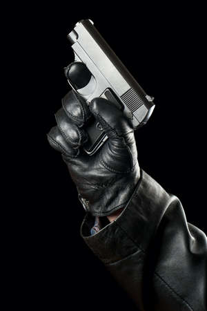 Gun in the hand of a bandit wearing gloves on a black background